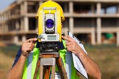 Land surveyor theodolite. Land surveyor looking through theodolite at construction site stock image