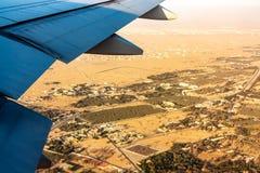 Land under vingen av ett flygplan från en höjd av flyget Öken by, trän, fält Förbluffa sikt från fönstret av royaltyfria bilder