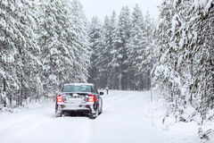 Land vehicle driving on a country road in wintry forest Royalty Free Stock Images
