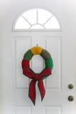 Land-Weihnachtskranz, der an der weißen Tür hängt Lizenzfreie Stockfotografie