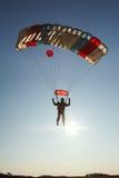 Landa en skydiver mot panelljus Royaltyfri Foto