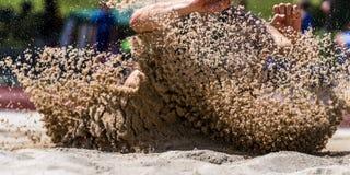 Landa i längdhopp i friidrott Royaltyfri Foto