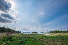 Landa och gräs med berget och trevlig himmelbakgrund Royaltyfri Bild