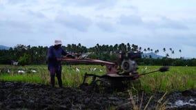 Landarbeiter benutzt den Handtraktor, der Maschine pflügt, um sich für das Reispflanzen vorzubereiten stock video footage