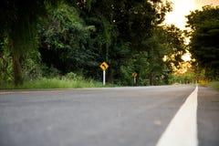 LandAsphaltstraße mit Verkehrszeichen zum Wald Lizenzfreie Stockfotos