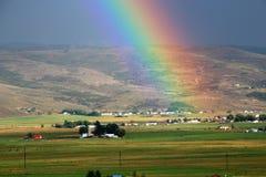 Landbauernhof, -feld und -regenbogen Stockbild