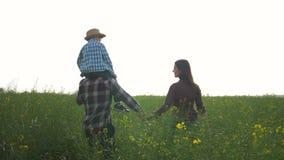 Landbouw, jonge mens met kindjongen op schouders en vrouwelijke gang op groen raapzaadgebied tegen heldere hemel stock footage