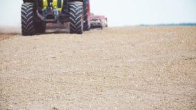 LANDBOUW - Landbouwtrekker die en gebied zaaien cultiveren stock videobeelden