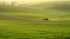 Landbouw op de rollende heuvels van Moravië met tarwe filds en tractor Royalty-vrije Stock Foto's