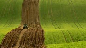 Landbouw op de rollende heuvels van Moravië met tarwe filds en tractor Stock Fotografie