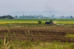 Landbouw ploegende tractor op de gebieden van het tarwegraangewas Stock Afbeeldingen