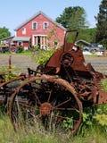 Landbouwbedrijf: rode schuur met oude machines Stock Afbeeldingen