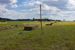 landbouwbedrijfgebied met hey vork en machine onder blauwe hemel Stock Foto's