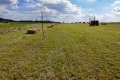 landbouwbedrijfgebied met hey vork en machine onder blauwe hemel Royalty-vrije Stock Afbeelding