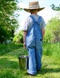 Landbouwbedrijfjongen met melkende emmer royalty-vrije stock afbeelding