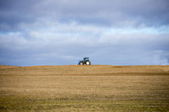 Landbouwbedrijftractor op breed open gewassengebied Royalty-vrije Stock Afbeeldingen