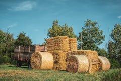 Landbouwbedrijftractor van hooibergen wordt gemaakt die stock afbeeldingen