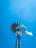 Landbouwbedrijfwindmolen tegen een duidelijke blauwe hemel Stock Foto