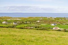Landbouwbedrijven en huizen in het Fanore-dorp met Aran Islands in rug stock foto's