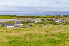 Landbouwbedrijven en huizen in het Fanore-dorp met de baai van Galway in backgr royalty-vrije stock afbeelding