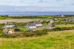 Landbouwbedrijven en huizen in het Fanore-dorp met de baai van Galway in backgr stock afbeeldingen