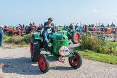 Landbouwer in blauw GLB en jeans op groene tractor royalty-vrije stock fotografie