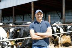 Landbouwer die aan landbouwbedrijf met melkkoeien werken royalty-vrije stock foto's