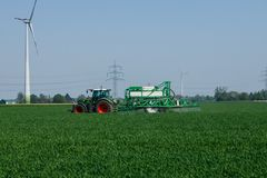 Landbouwer die de gebieden in de lente naast reusachtige windturbines werken royalty-vrije stock fotografie
