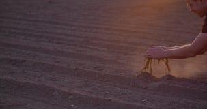 Landbouwer die grond in handen onderzoeken, landbouw de landbouwachtergrond stock footage