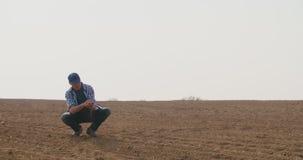 Landbouwer die grondkwaliteit op vers gecultiveerd gebied onderzoeken stock videobeelden