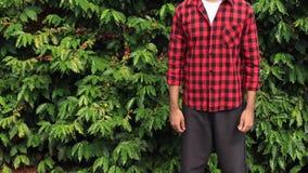 Landbouwer die met hoed in het gebiedslandschap van de koffieaanplanting glimlachen stock videobeelden