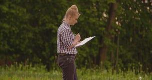 Landbouwer die met klembord installaties onderzoeken tijdens winderige dag stock video