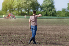 Landbouwer die met schoffel lopen stock fotografie