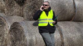 Landbouwer die met smartphone dichtbij de hooibalen spreken stock video