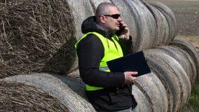 Landbouwer die op smartphone dichtbij de hooibalen spreken stock videobeelden
