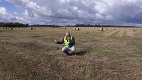 Landbouwer die op smartphone op het gebied dichtbij strobalen spreekt stock footage