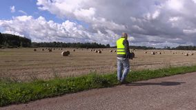 Landbouwer die op smartphone spreekt en op de weg dichtbij strobalen weggaat stock footage