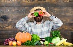 Landbouwer die pret houten achtergrond hebben De peperoogst van de mensengreep als grappig emotioneel grimas Het concept van de p stock afbeeldingen