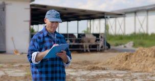 Landbouwer die terwijl het schrijven op klembord tegen schuur gesturing stock videobeelden