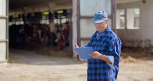 Landbouwer die terwijl het schrijven op klembord tegen schuur gesturing stock video