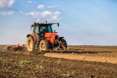 Landbouwer die in tractor land met zaadbedlandbouwer voorbereiden stock foto's