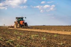 Landbouwer die in tractor land met zaadbedlandbouwer voorbereiden stock afbeeldingen