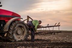 Landbouwer die in tractor land met zaadbedlandbouwer voorbereiden stock fotografie