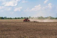 Landbouwer die in tractor land met zaadbedlandbouwer voorbereiden royalty-vrije stock afbeelding