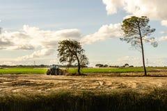Landbouwer die in tractor land met zaadbedlandbouwer voorbereiden Zonsondergang royalty-vrije stock afbeeldingen