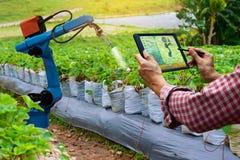 Landbouwer die van het de robotwerk van het tablet slimme wapen landbouwmachines houden stock afbeelding