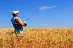 Landbouwer die voor tarwe vist Stock Foto