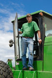 Landbouwer die zich in tractordeuropening bevindt Royalty-vrije Stock Foto