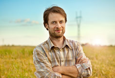 Landbouwer die zich trots voor zijn tarwegebieden bevinden royalty-vrije stock afbeelding