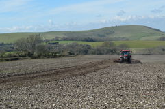 Landbouwer die zijn gewassengebied in Sussex werken Stock Fotografie